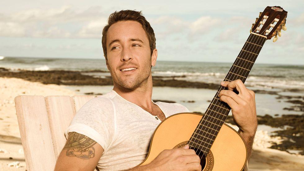 Alex OLaughlin of Hawaii Five 0 on beach playing guitar