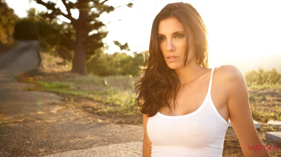 Daniela Ruah of NCIS Los Angeles in tank top with sun behind her