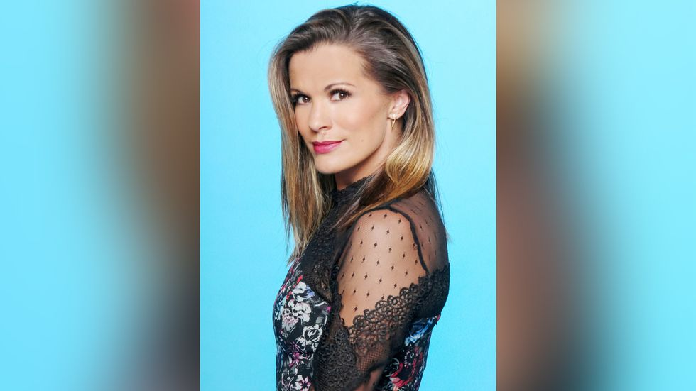 Melissa Claire Egan wears a lacey top and looks squarely at the camera.