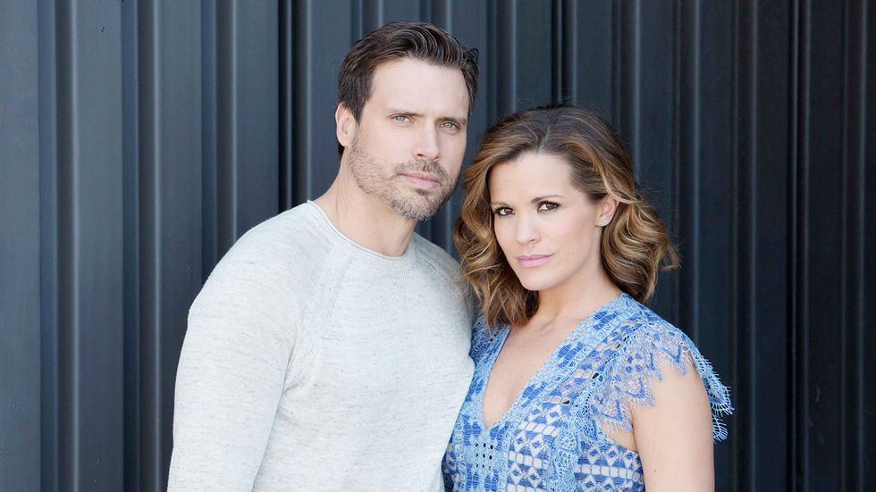 Melissa Claire Egan poses with a cast mate in front of a blue wall,