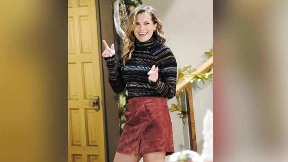 Melissa Claire Egan smiles and does finger guns to the camera.
