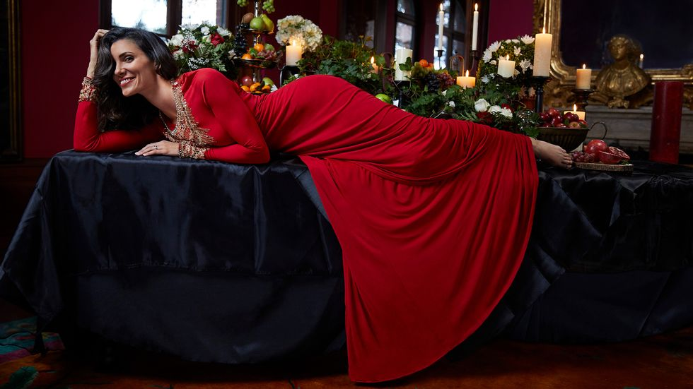 Daniela Ruah in a red dress laying on a table