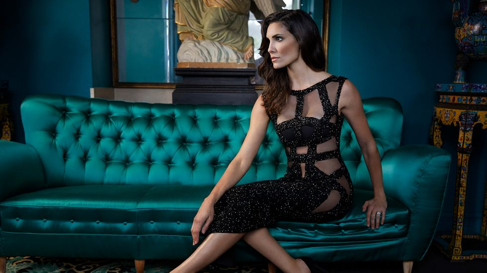 Daniela Ruah in a strappy black dress on a teal couch