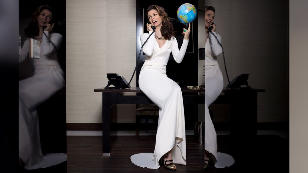 Bridget Moynahan in long white dress holding a globe