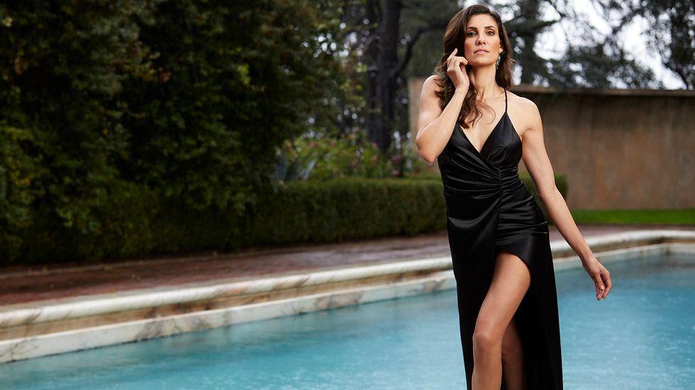 Daniela Ruah of NCIS Los Angeles in black satin dress by pool