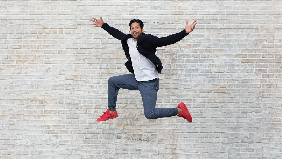 Adam Rodriguez jumps with red sneakers