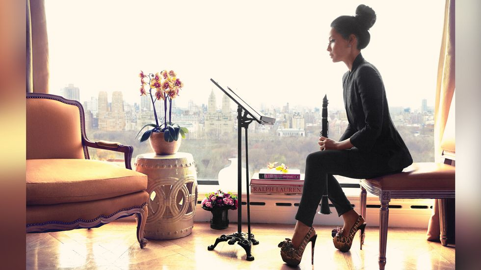 Lucy Liu playing the clarinet over looking NYC