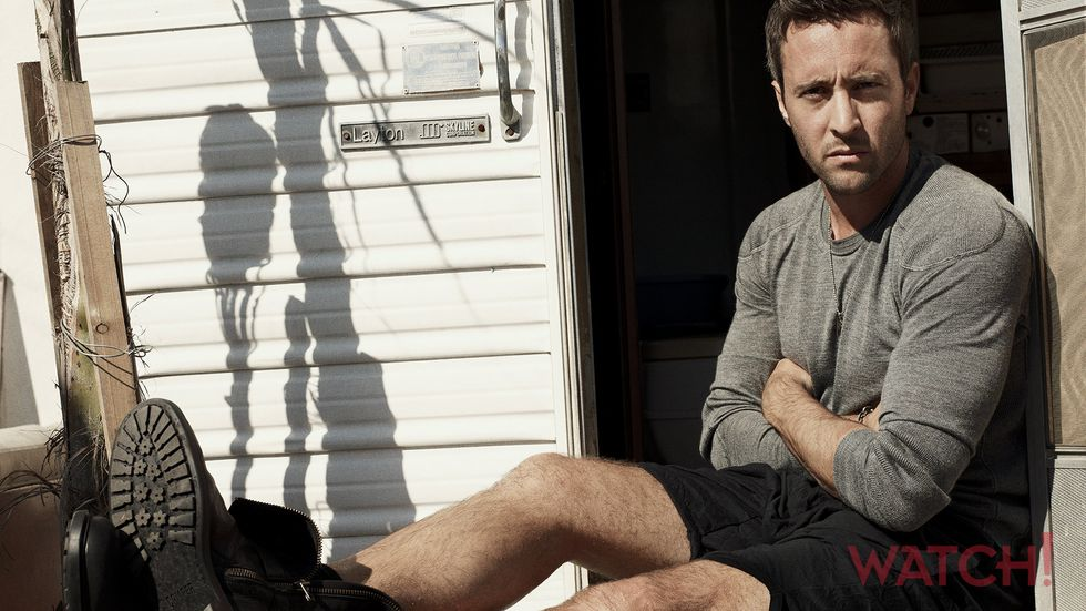 Alex OLoughlin of Hawaii Five 0 in gray long sleeved t shirt and black shorts
