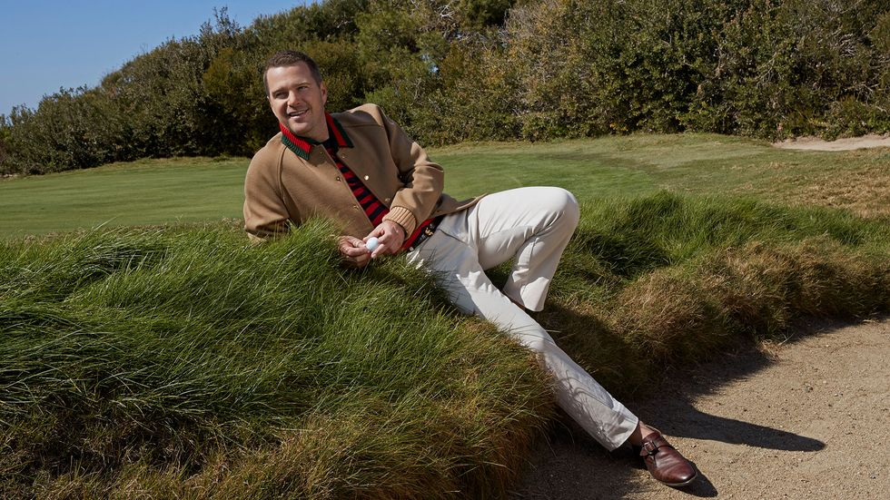 Chris O'Donnell reclines on the edge of a golf sand trap.