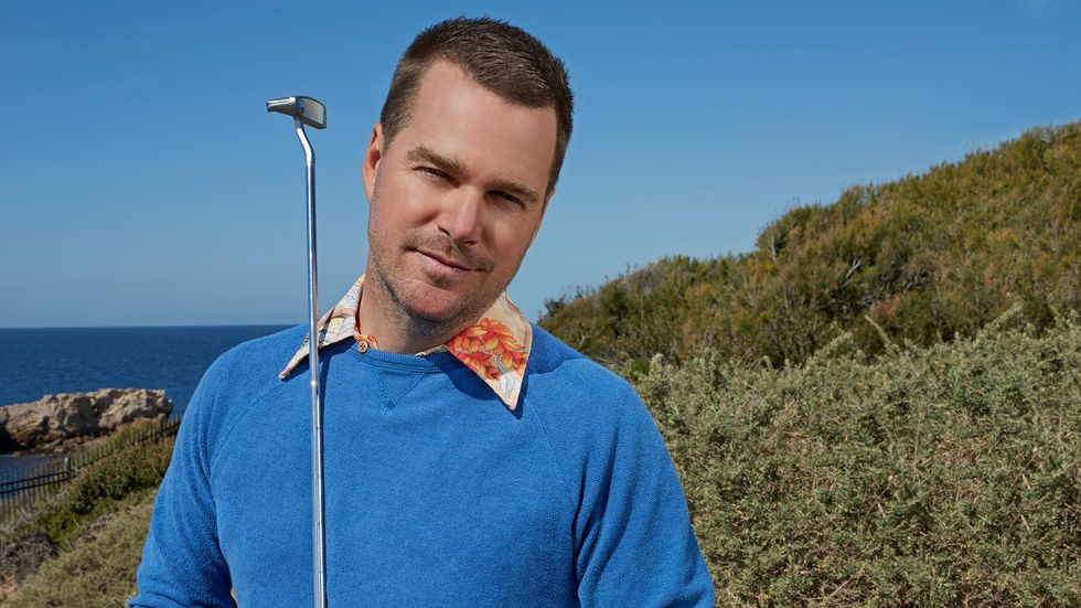 Chris O'Donnell wears a blue sweatshirt with a flowered collar while standing on a golf course.