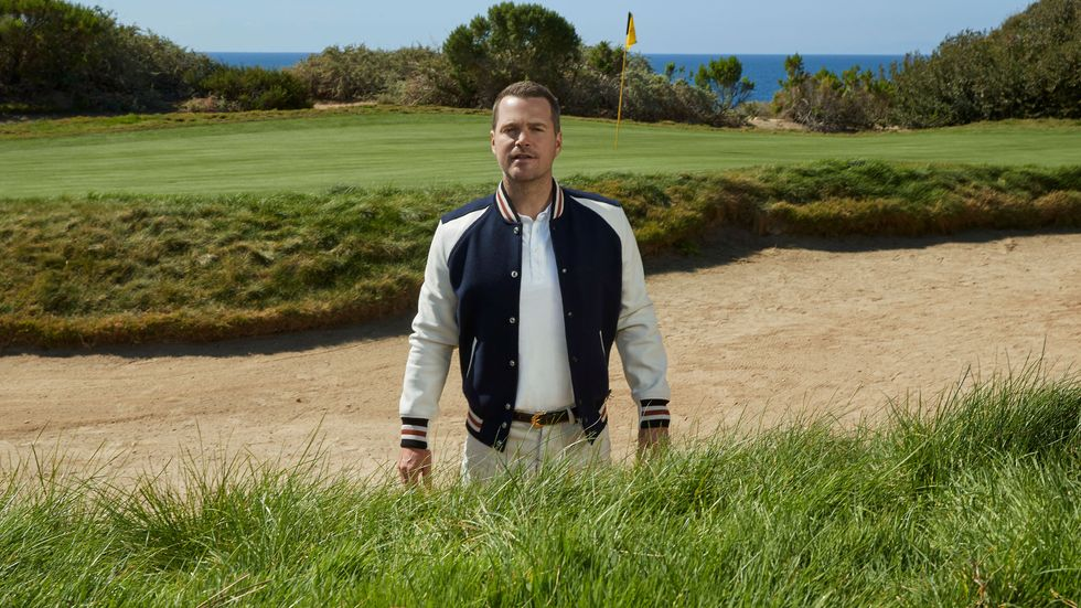 Chris O'Donnell wears a letterman's jacket as he stands in a sand trap of a golf course.