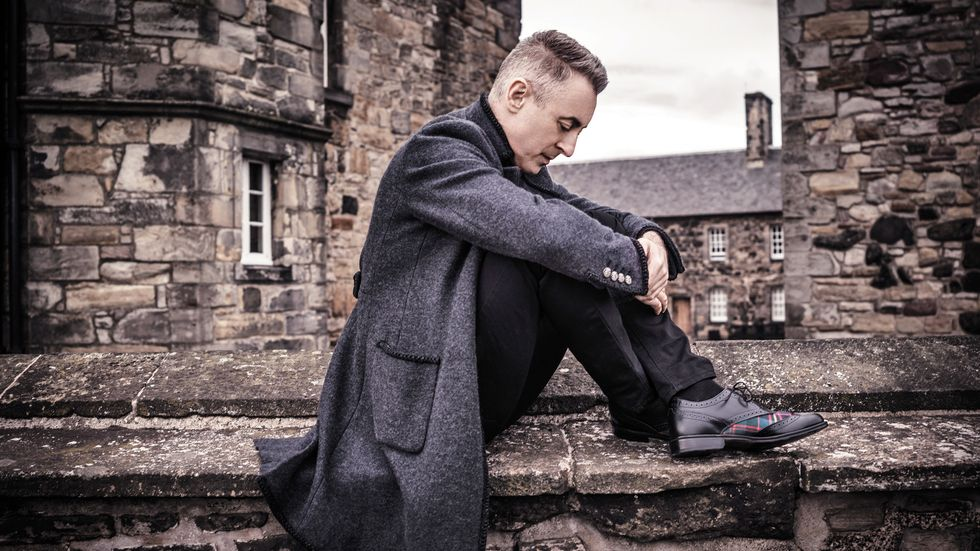Alan Cumming in a wool longcoat on a stone rooftop