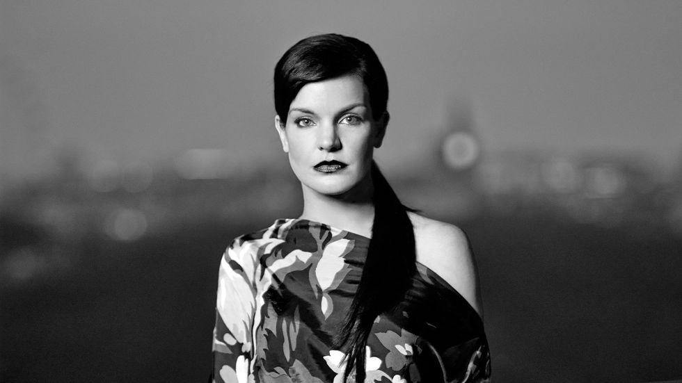 Black and white image of Actress Pauley Perrete in a floral print dress.