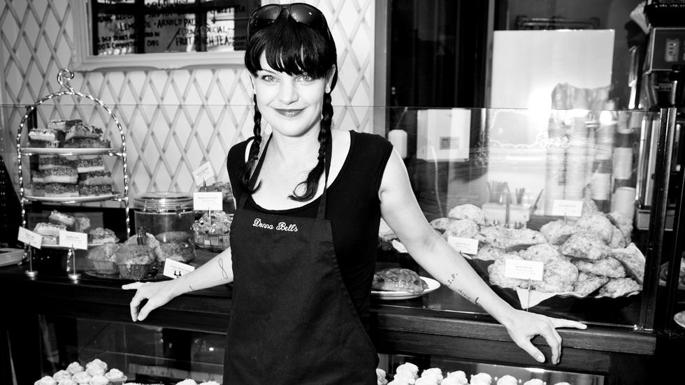 Black and white image of Actress Pauley Perrete wearing an apron in front of baked goods.