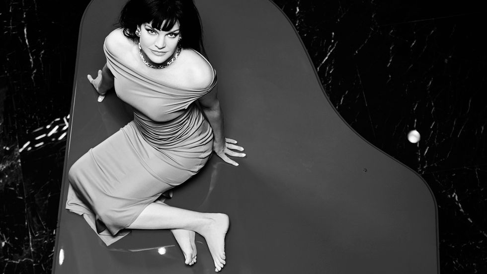 Black and white image of Actress Pauley Perrete in a sheer off the shoulder dress.