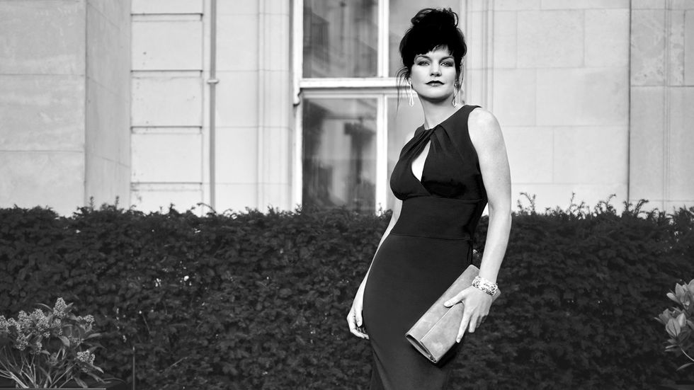 Black and white image of Actress Pauley Perrete in a form-fitting black dress.
