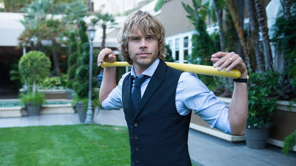 Eric Christian Olsen wearing a vest and resting his arms on a wiffle bat