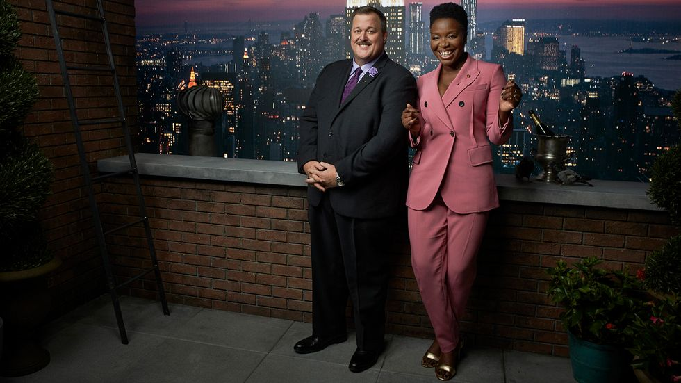 Billy Gardell and Folake Olowofoyeku in front of the Manhattan skyline