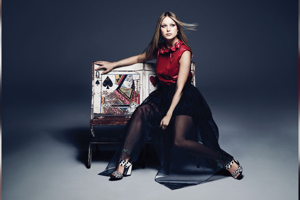 Melissa Benoist sits on a styized playing card bench.