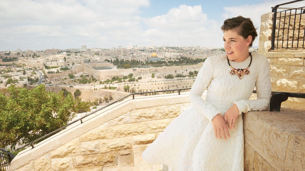 Mayim Bialik taking in the sights at Mount of Olives wearing a long sleeve white gown