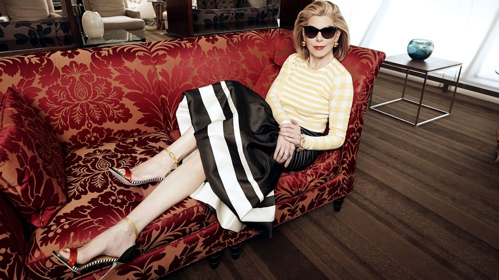 Christine Baranski wears shades relaxing on red couch