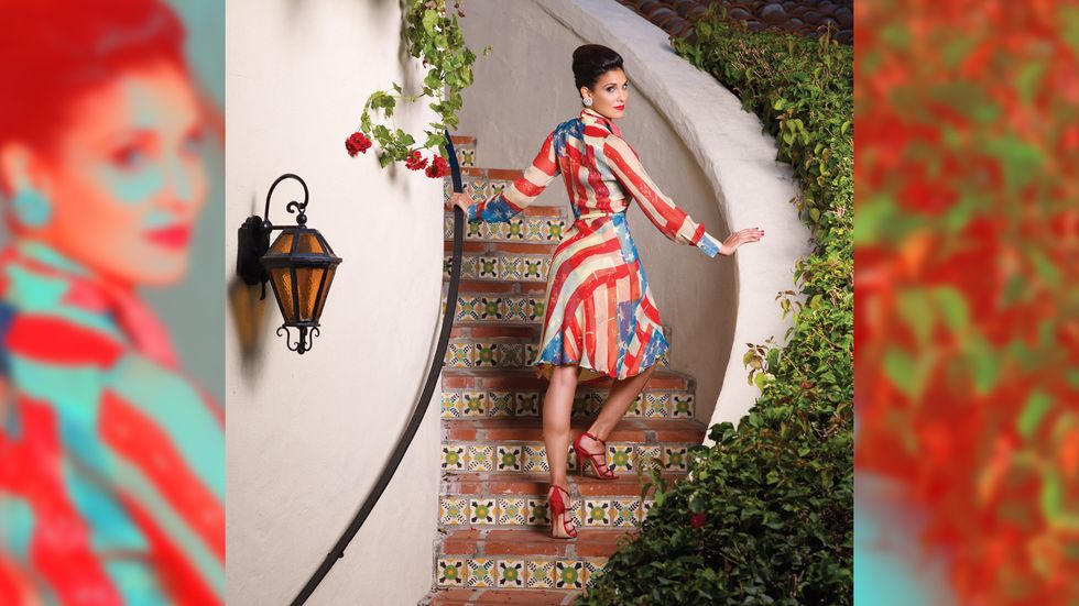 Daniela Ruah in red white and blue dress on staircase