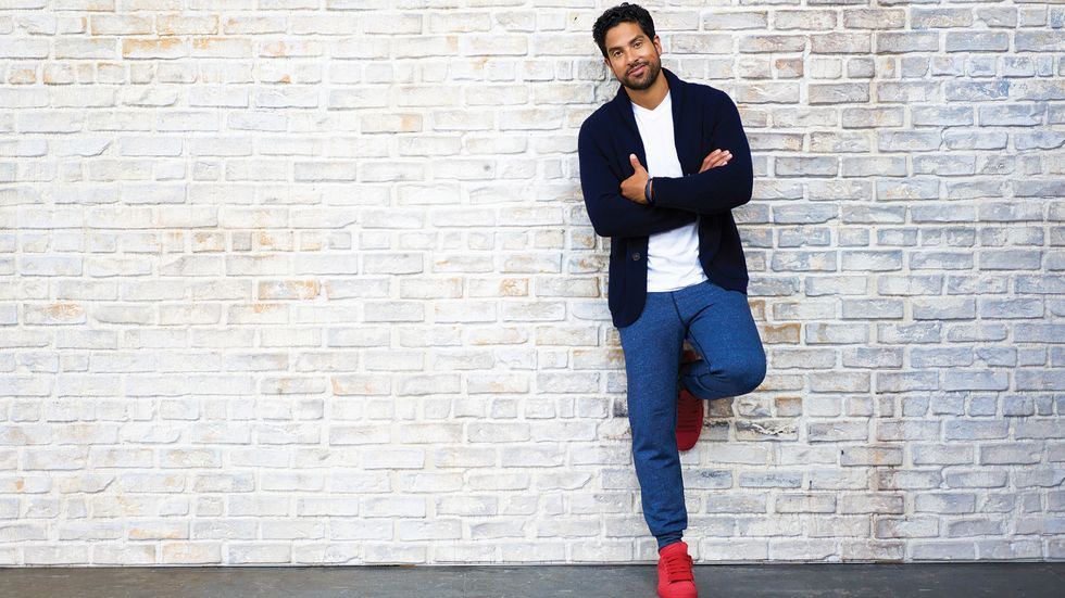 Adam Rodriguez wearing red sneakers against white brick wall