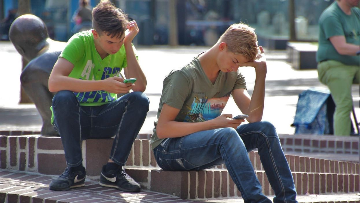 Young men using their phones outdoors