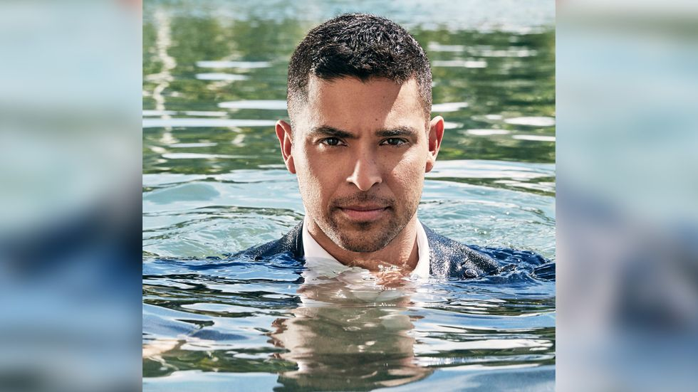 Wilmer Valderrama fully dressed n a pool of water with his head just above the water
