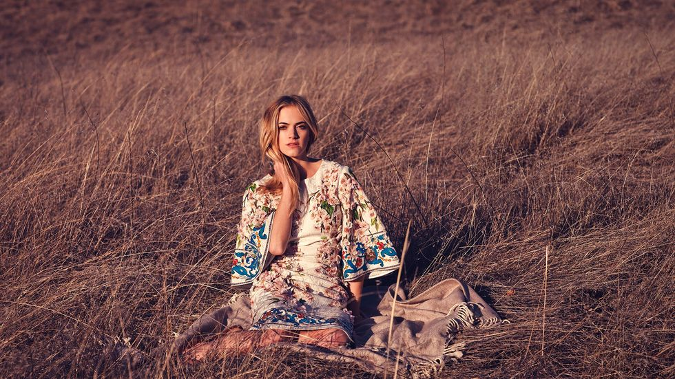 Emily Wickersham is in a white and colorfully floral dress has her hand on her neck as she sits in a field of tall dry grass