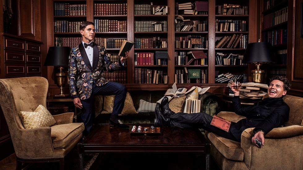 In a library there is Brian Dietzen on a couch with a book in his lap and a drink in hand and another Brian Dietzen across the room with his foot on the coffee table and a book in hand