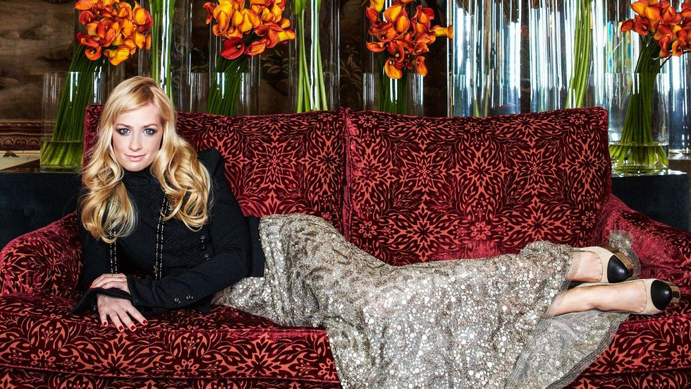 Beth Behrs lounges in style on red couch