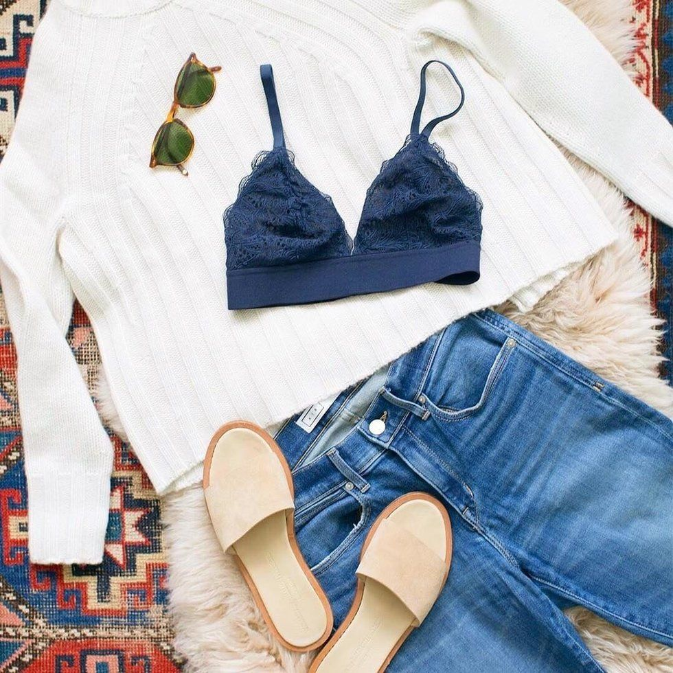 white sweater and a navy blue bralette are layed out on an aztec rug