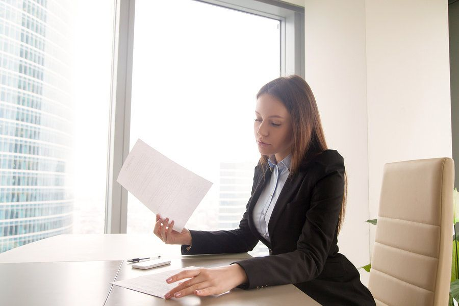 A hiring manager goes through job applications with outdated phrases you should never include on resumes