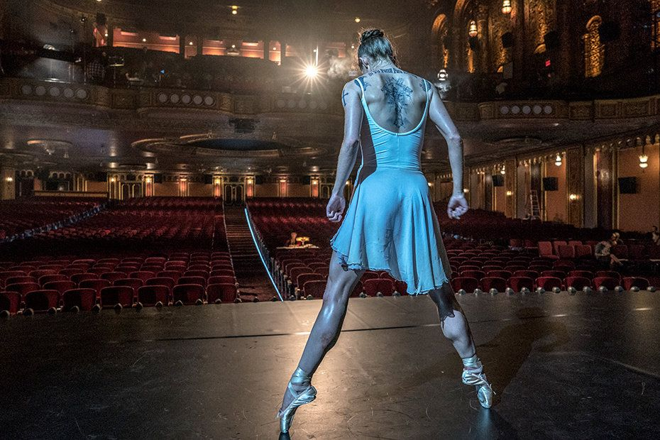 A thin white woman in pointe shoes and a white leotard and skirt ensemble balances en pointe in second position. Her arms are at her side, elbows pulled back, and her head is dropped to look at the floor in front of her. Dark, intricate tattoos are visible across her back, above the edge of the scoop-back leotard. Beyond the stage, the red seats of an opulent theater are empty, save for a figure seated at a table midway in the orchestra.
