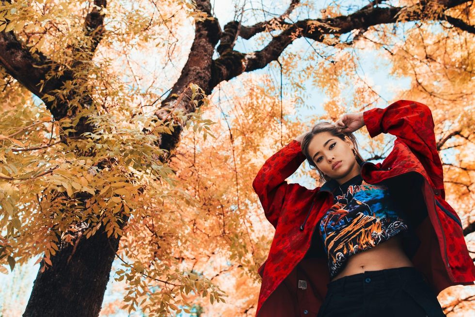 Woman underneath a tree with fall-colored leaves, looking down at camera