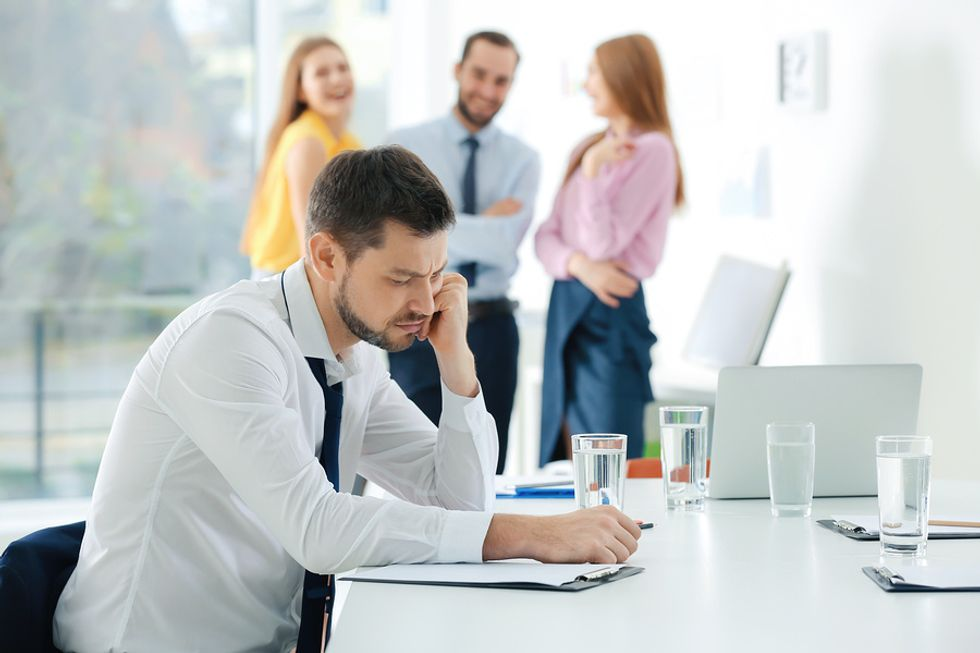 Young man looking sad at his desk as his co-workers laugh and talk behind him.