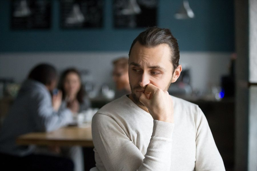 Introverted young man sitting separate from his co-workers in a break room.