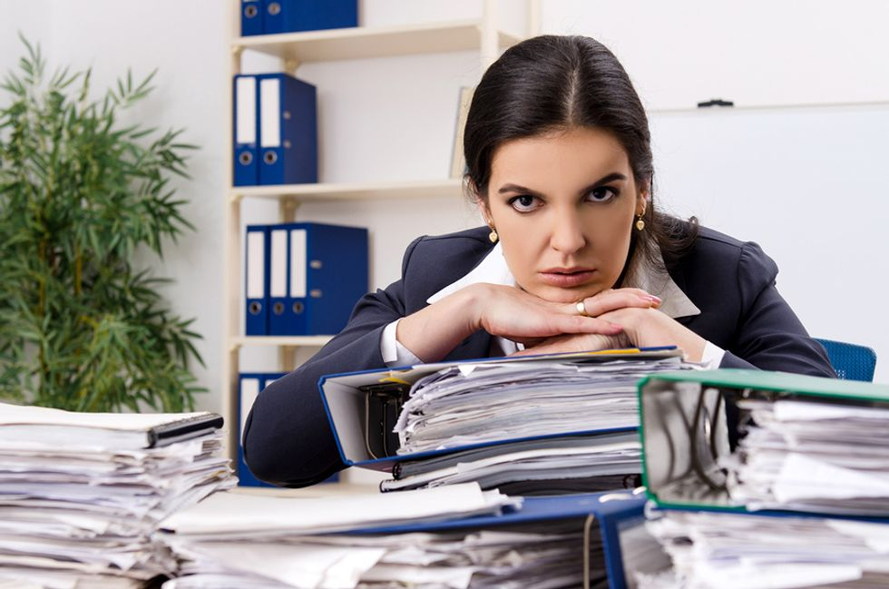Female employee looking unhappy with the work she has at her desk and deciding whether she should find a new job.