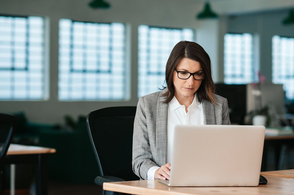 Business woman sitting at her desk and focusing on her most important tasks at work.