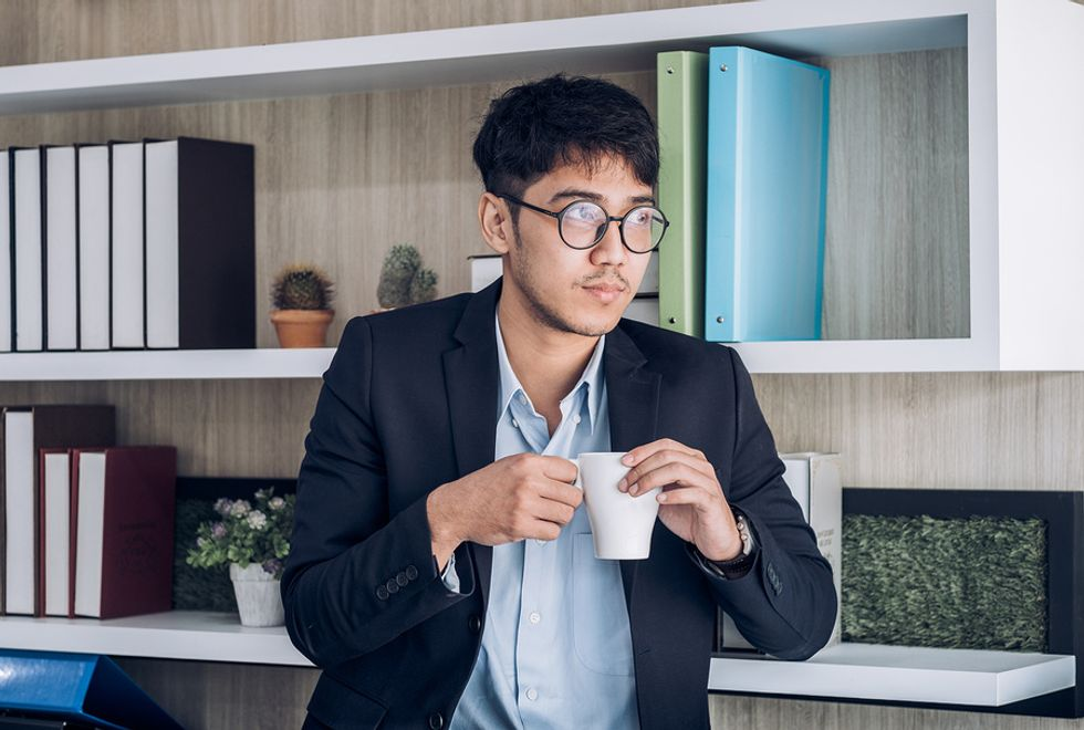 Young professional man drinking coffee and taking a break from work.