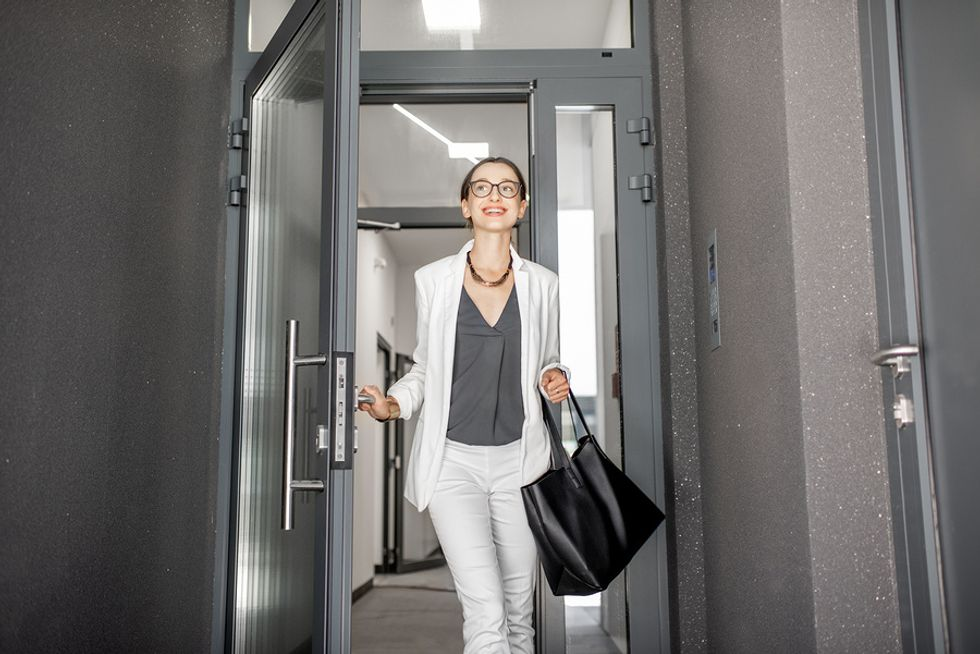 Young professional woman leaving her office and looking forward to her post-work plans.