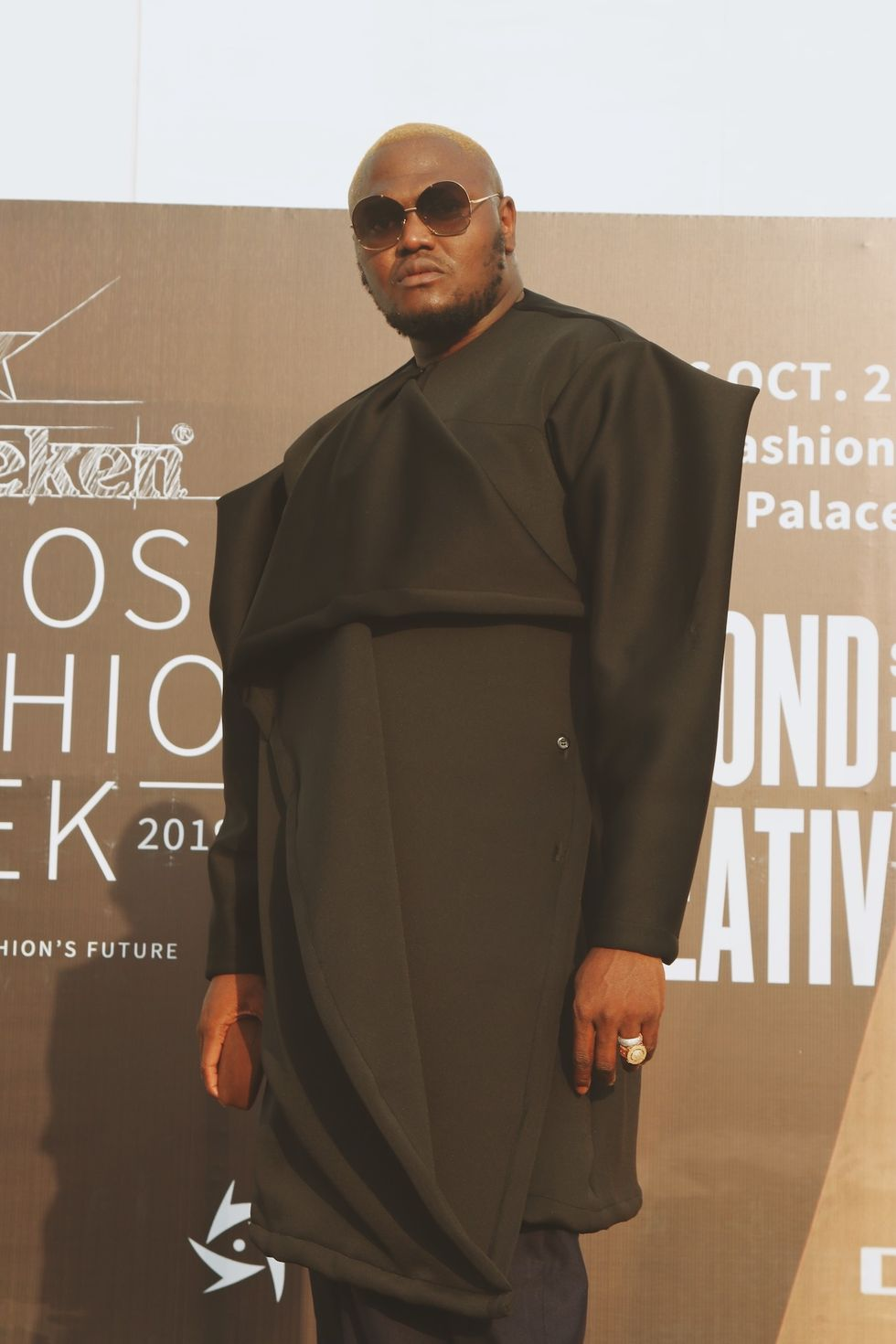 Tall Nigerian man wearing a structural black coat and big sunglasses at Lagos Fashion Week 2019