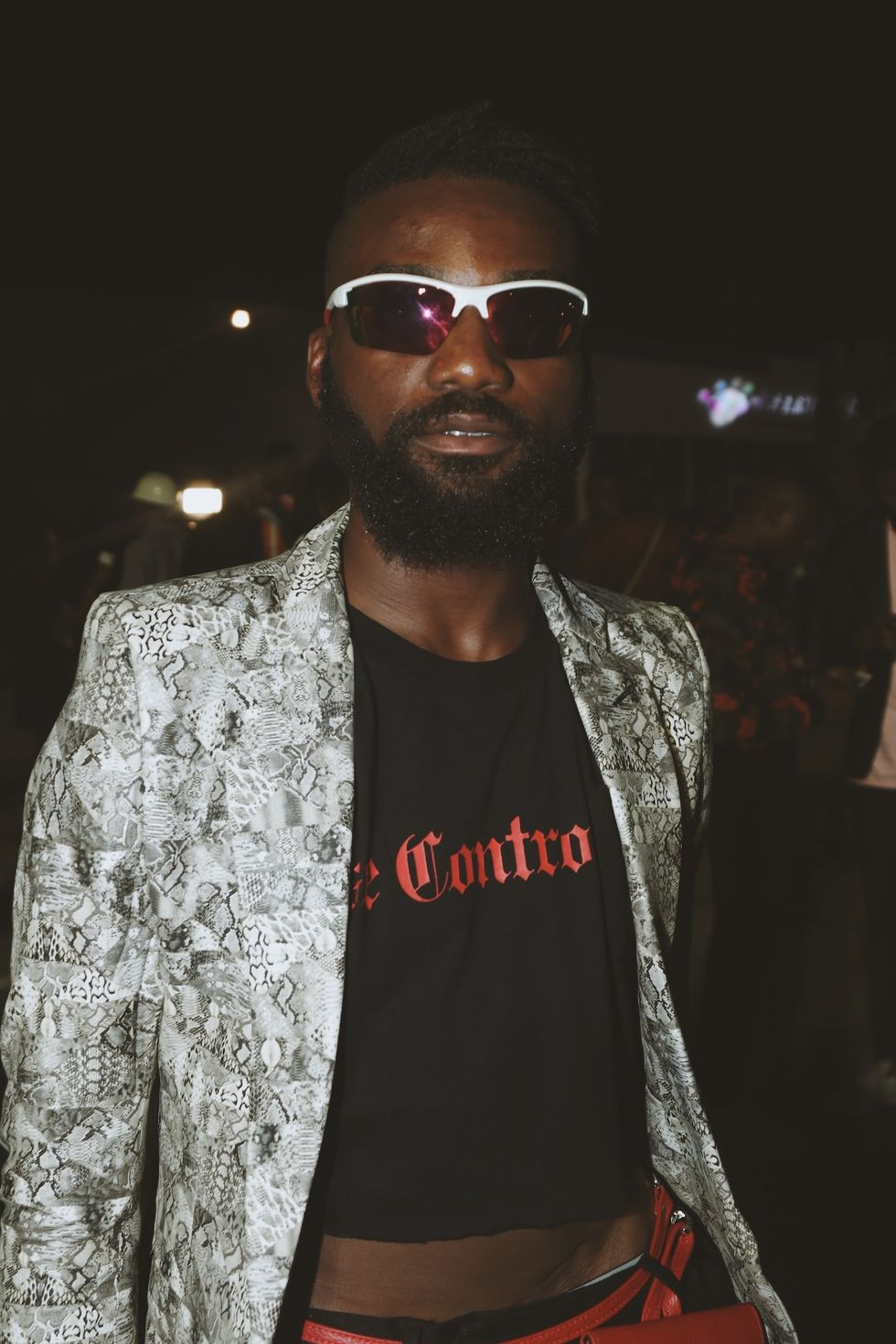 Nigerian man in snakeskin jacket, crop top and wraparound sunglasses at Lagos Fashion Week 2019.