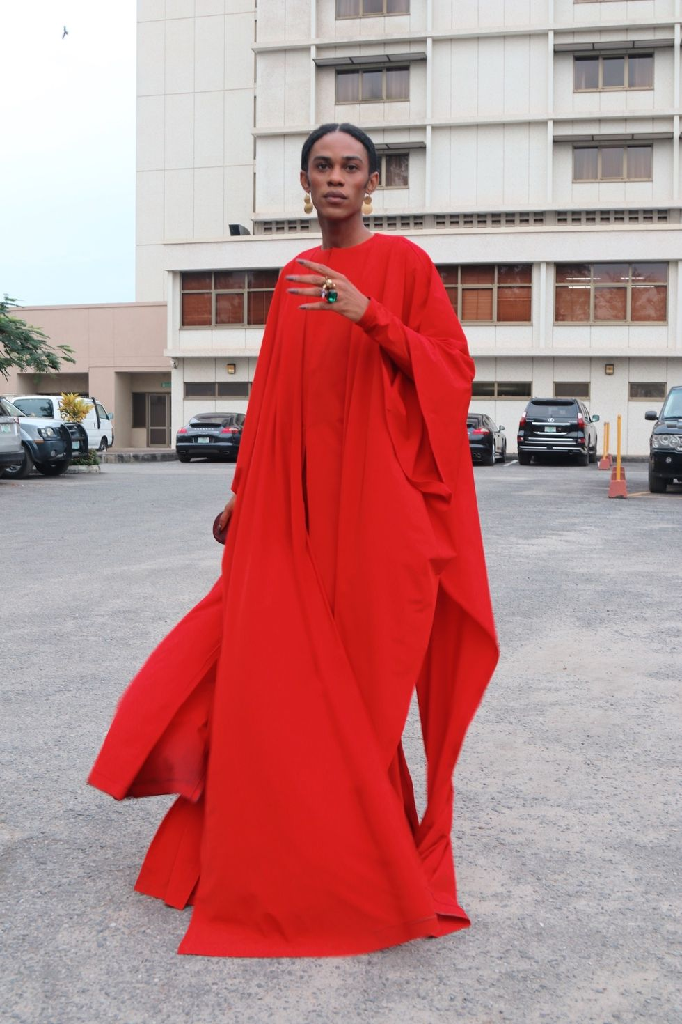 Nigerian man wearing a red dress and chunky jewelry at Nigerian fashion week.