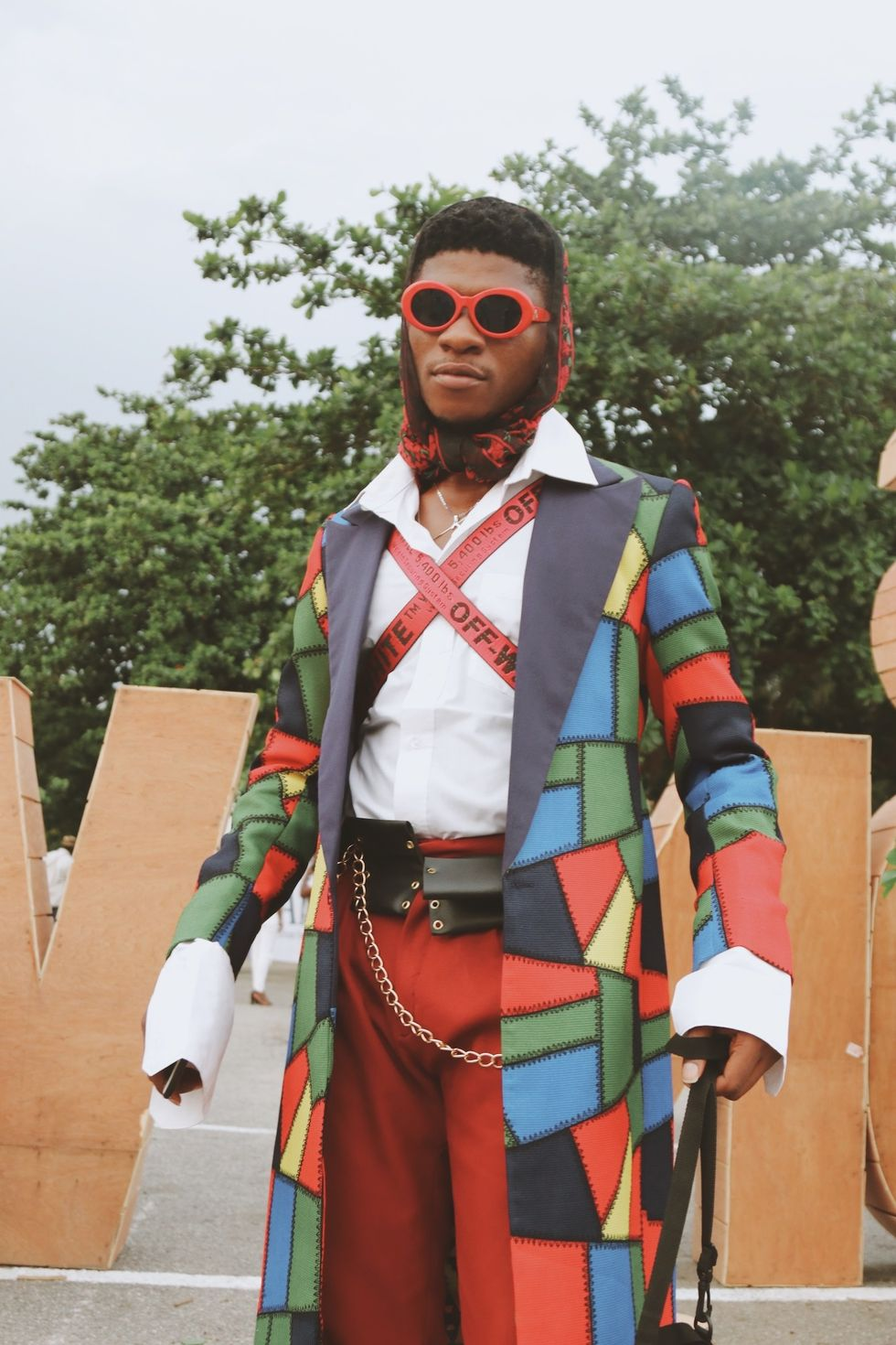 Nigerian man wearing colorful coat and red sunglasses.