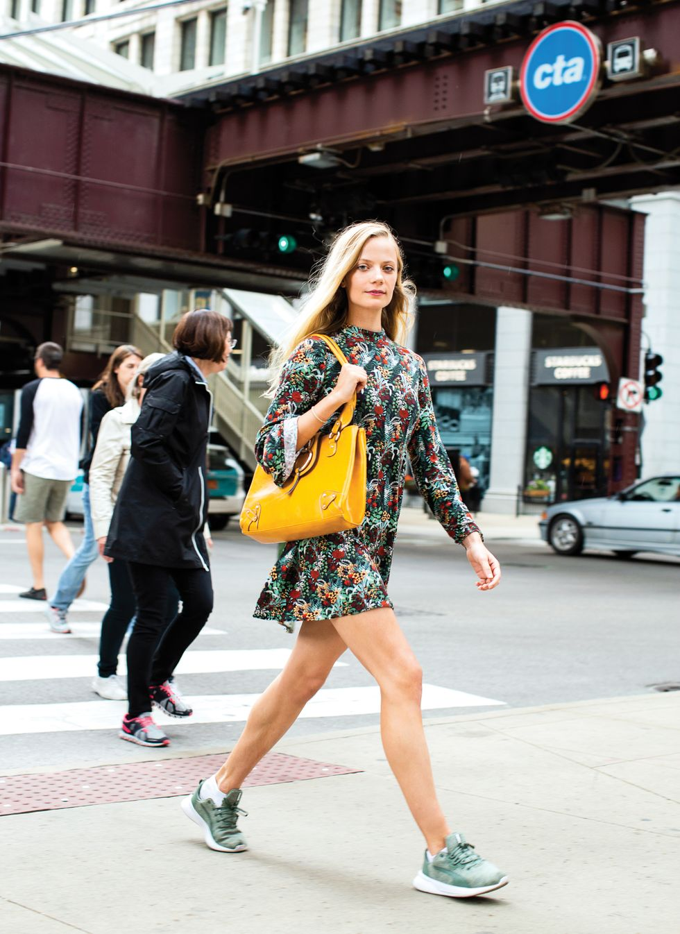 Woman with long blonde hair wearing green sneakers, a floral dress and carrying a large yellow purse walks with purpose on the Chicago streets pass a CTA station.
