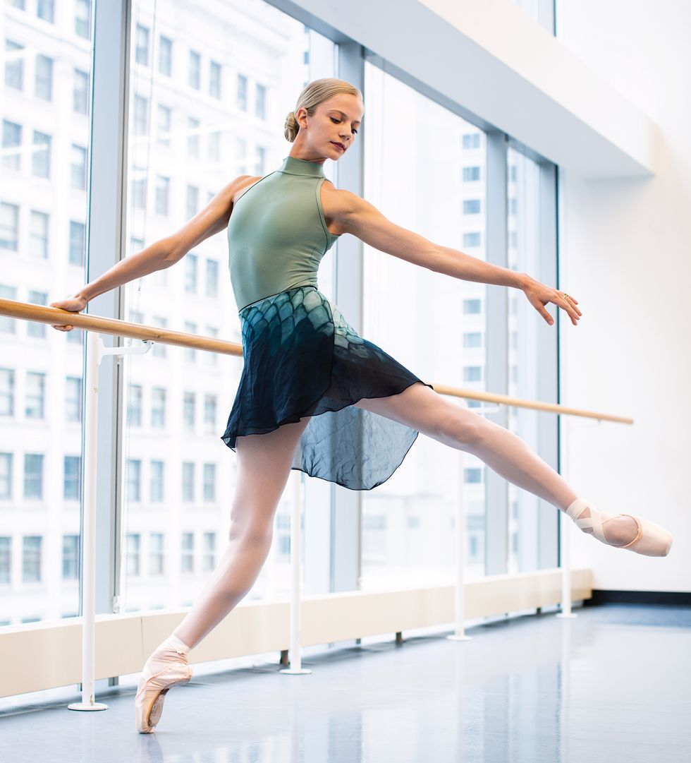 Brooke Linford wears a green, mockneck leotard and a sheer blue/green skirt, pink tights and pointe shoes. She holds a ballet barre in a bright, window filled studio and leans away in a low arabesque.