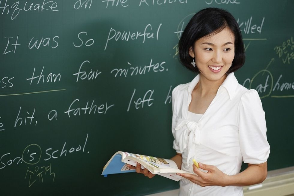 Young woman in front of a chalkboard teaching English overseas.