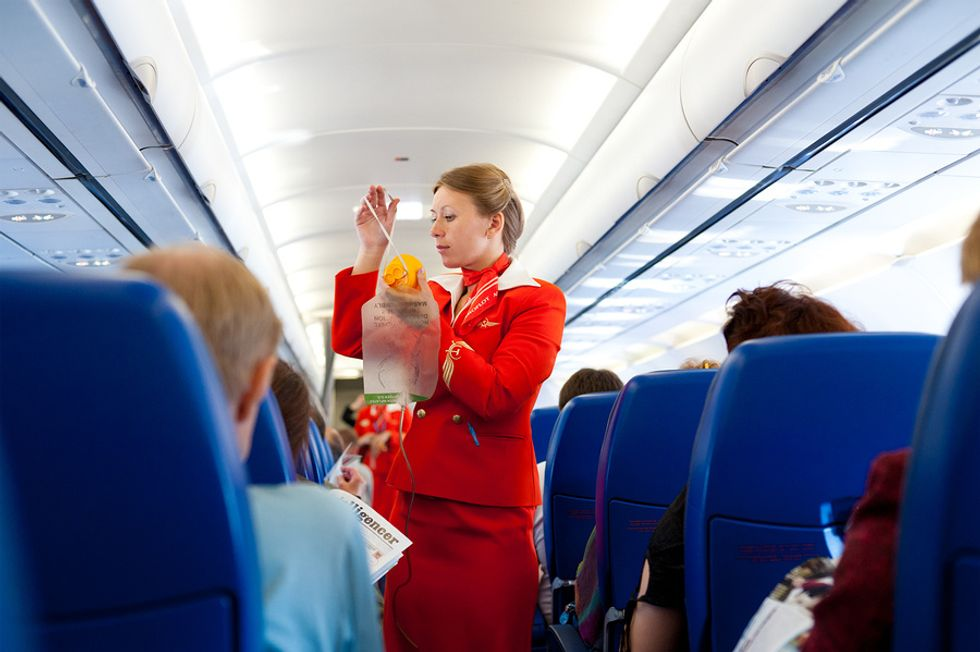 Female flight attendant showing passengers how to use their oxygen masks on an airplane.